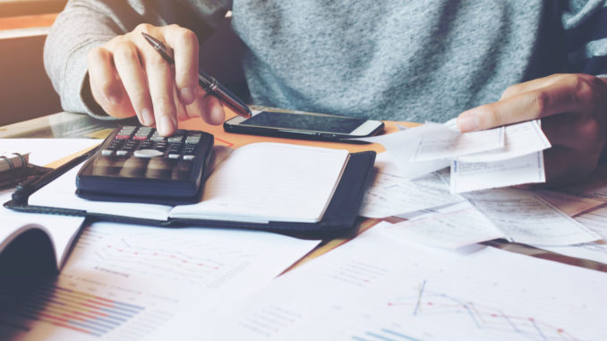 concept di note spese, zoom su mani con scontrini e calcolatrice